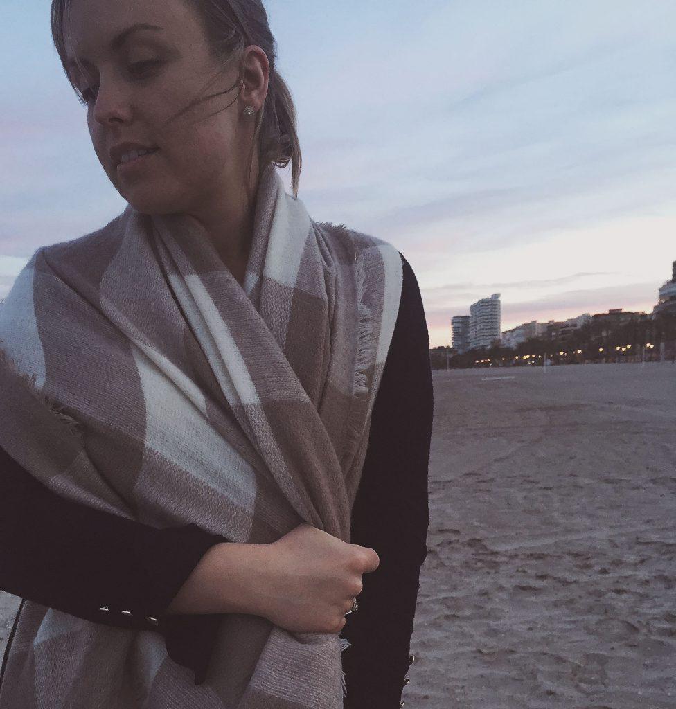 cozy in a scarf on playa san juan at dusk
